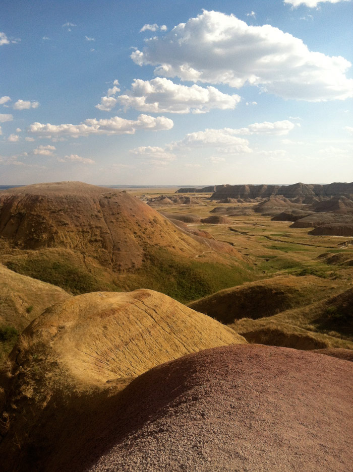 Photo of hills, prairie, and clouds at Conata Basin overlook, Badlands National Park