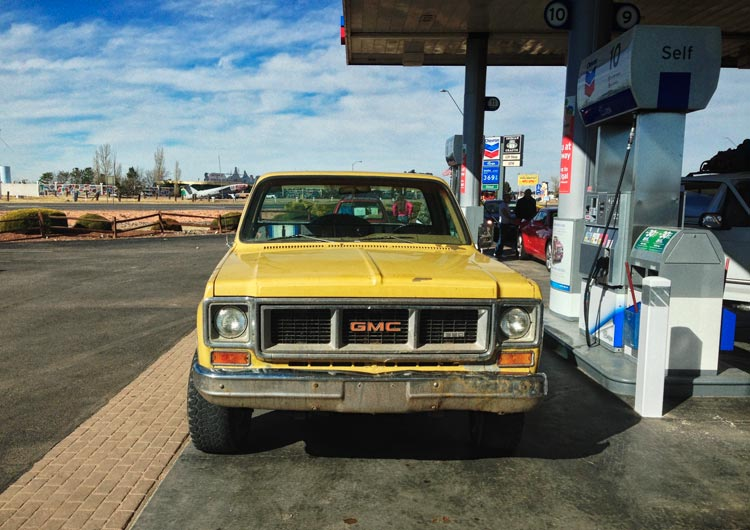Yellow GMC pickup truck at gas station.