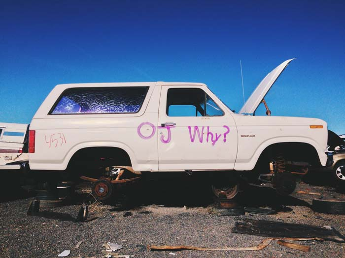 "White Ford Bronco in a junkyard, with the hood open, no wheels, and the text ""OJ why?"" spray-painted on the side"