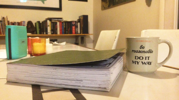 Photo of bound letter next to coffee mug